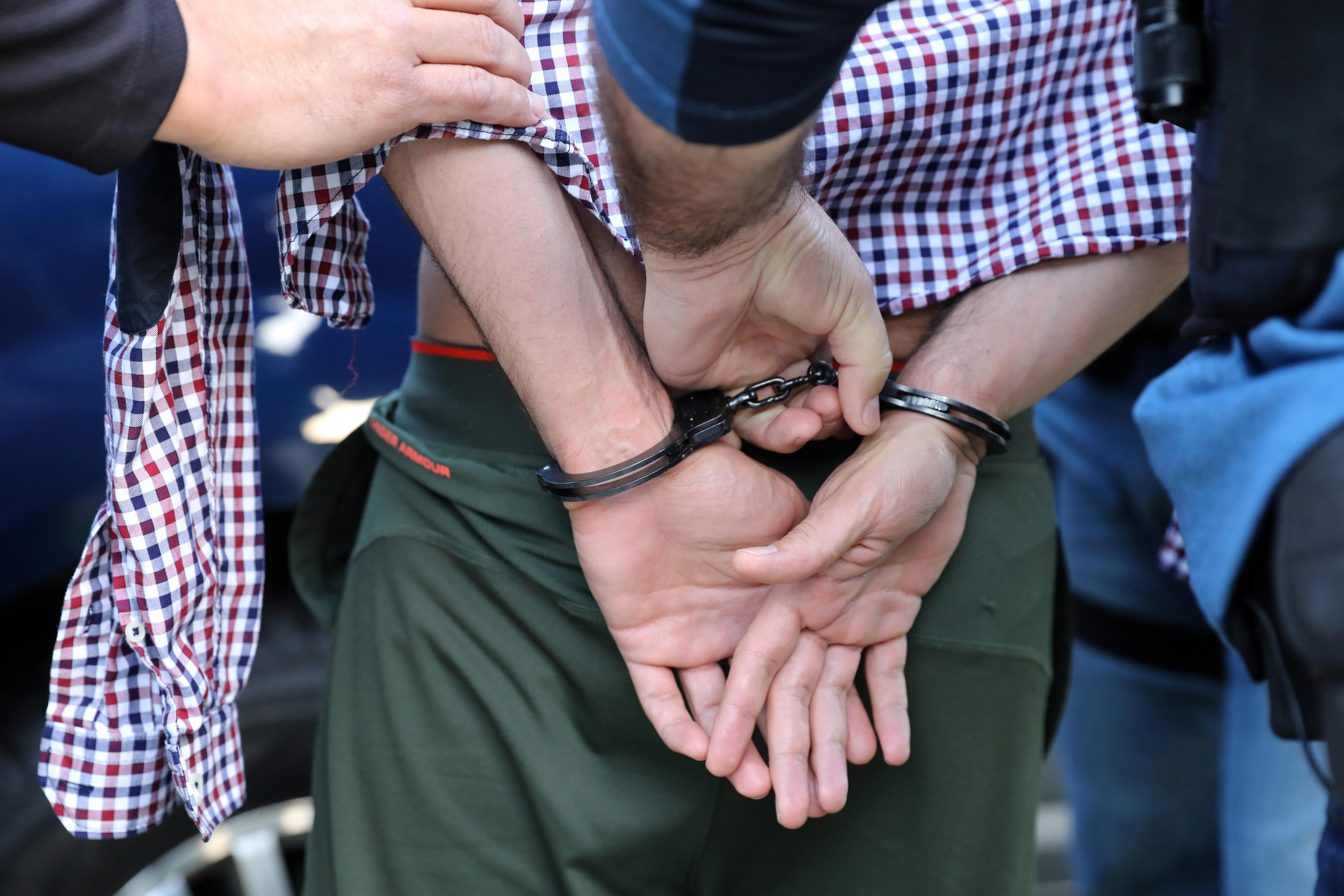 A man is handcuffed.