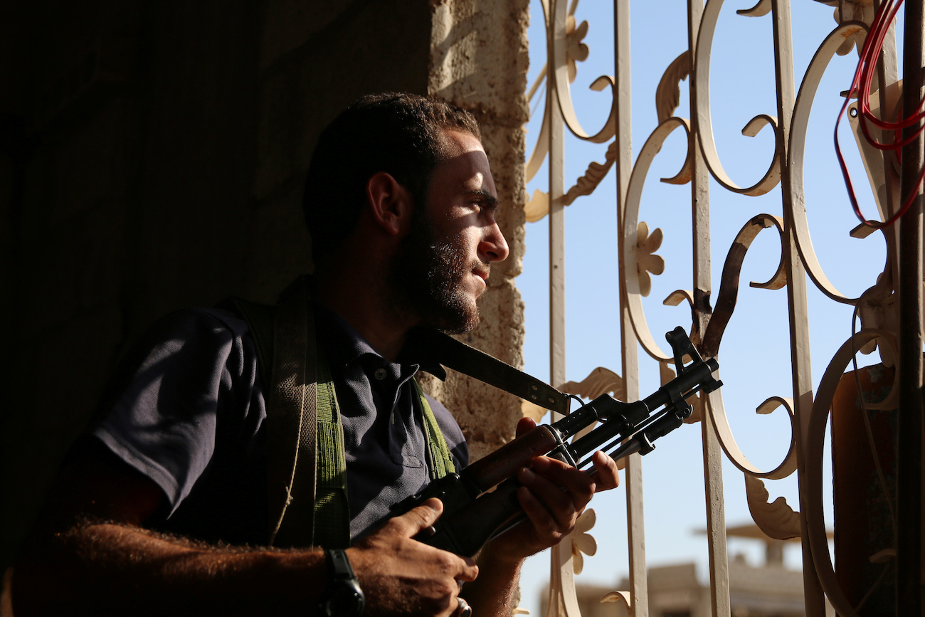 A Free Syrian Army fighter looks out through a window in rebel-held Al-Yadudah village, in Deraa Governorate, Syria, on July 19.