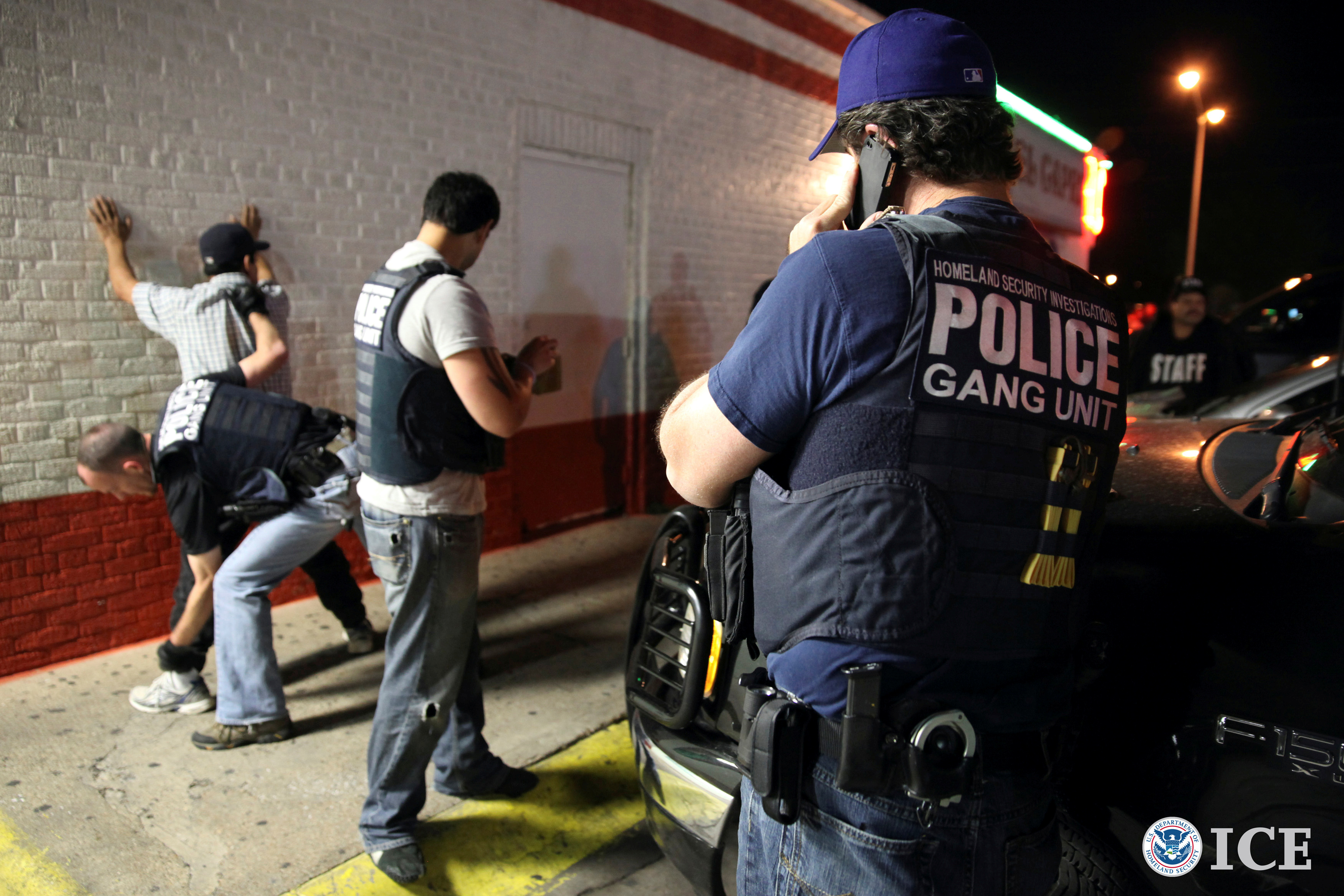 """Agents surround man up against a wall, on has """"Homeland Security Investigations POLICE Gang Unit"""" on his vest"""