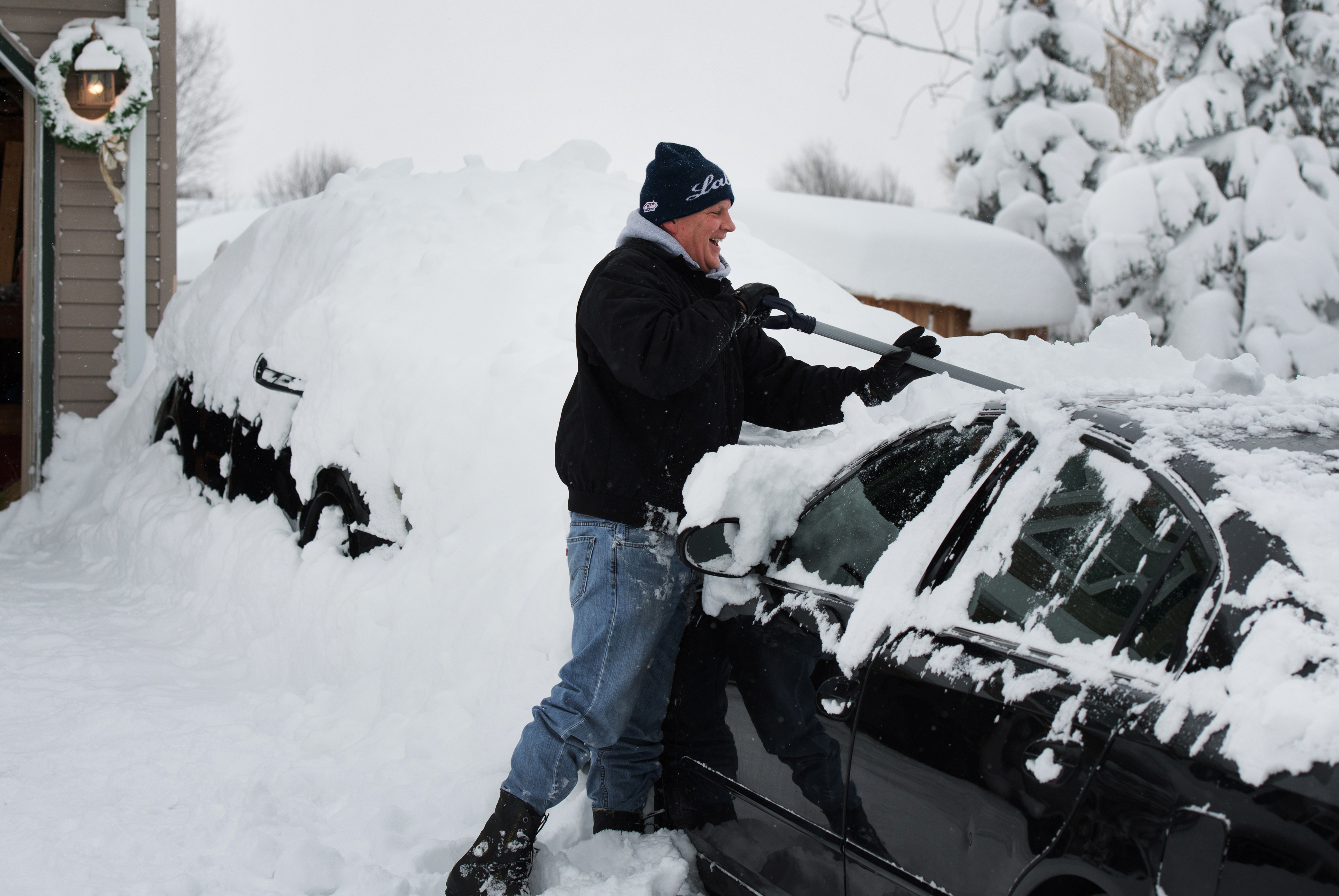 Jeff Strum removes snow off of his car