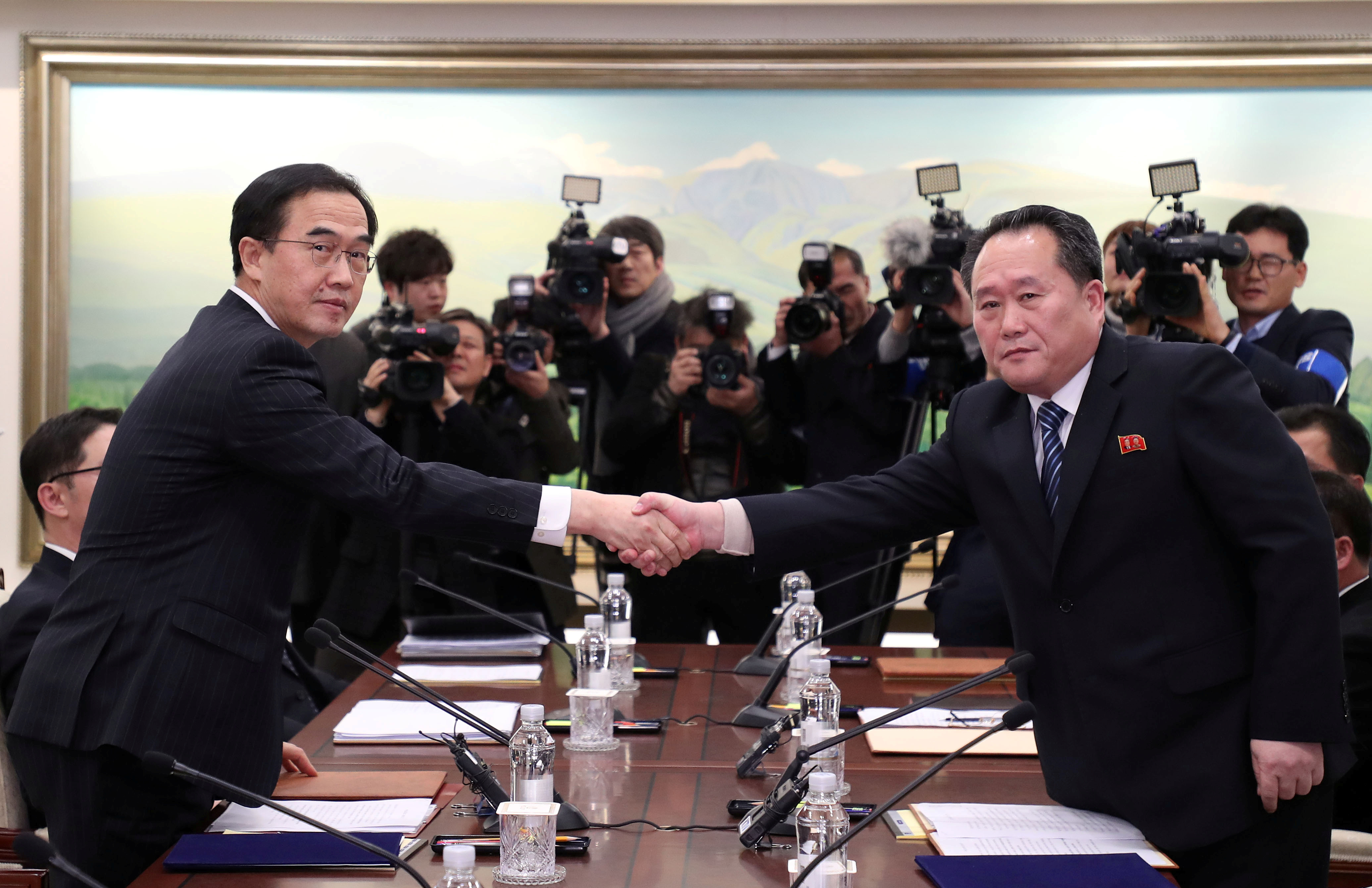 Head of the North Korean delegation, Ri Son Gwon (right) shakes hands with his South Korean counterpart Cho Myoung-gyon as they exchange documents after their meeting at the truce village of Panmunjom in the demilitarized zone separating the two Koreas on