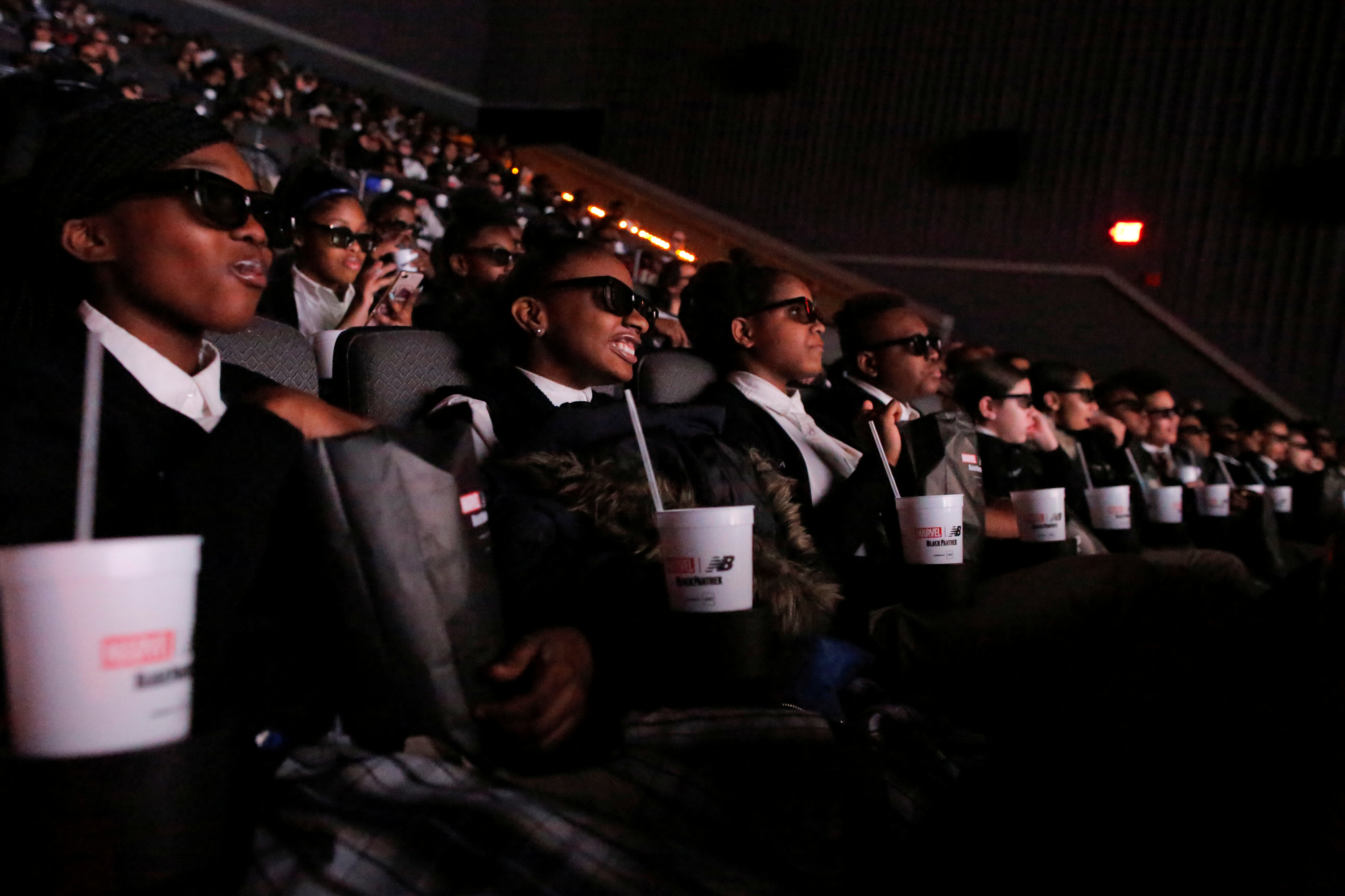 """Students from the Capital Preparatory Harlem School watch a screening of the film """"Black Panther"""" on its opening night."""