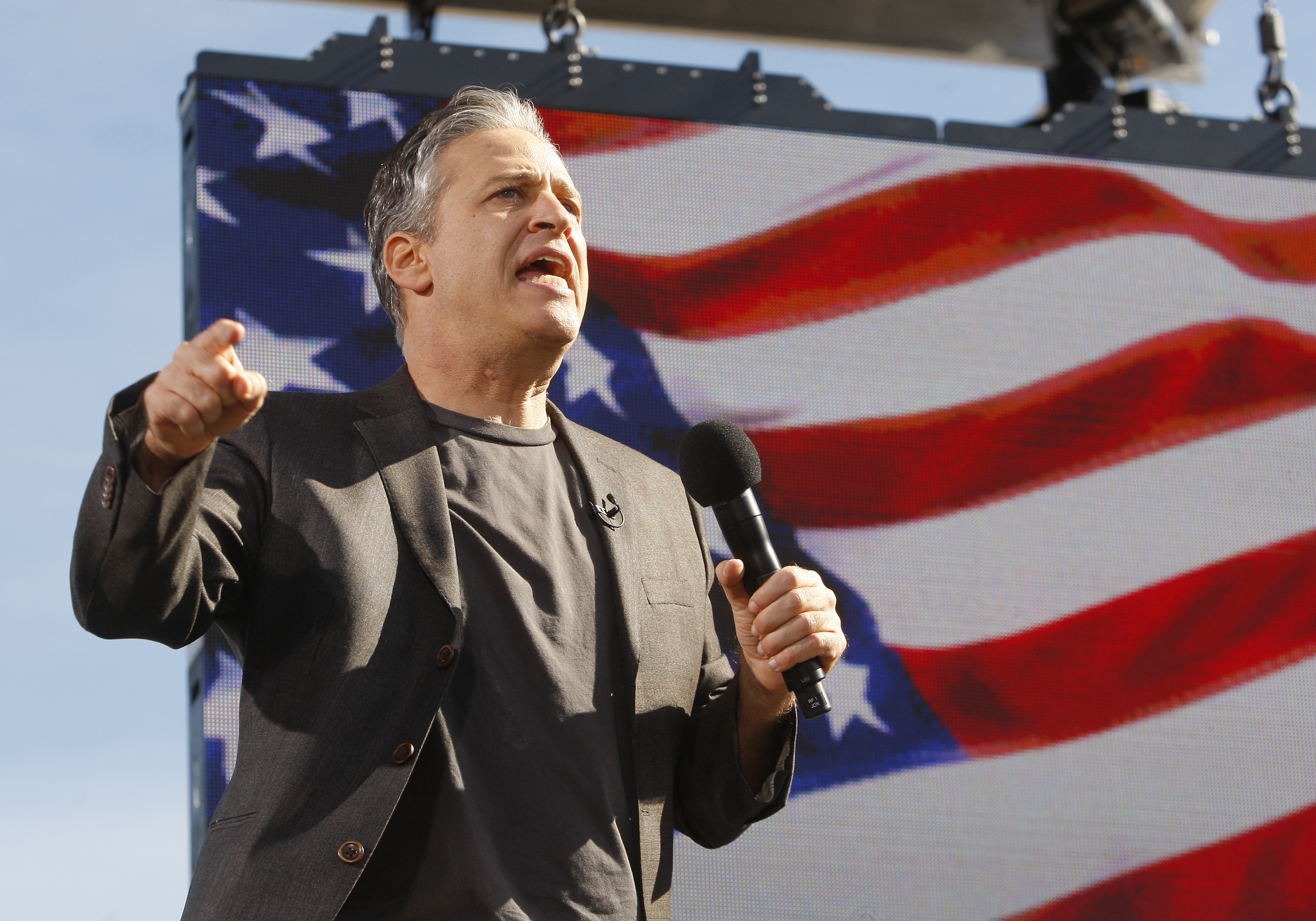 """Comedian Jon Stewart addresses the crowd during the """"Rally to Restore Sanity and/or Fear"""" in Washington, October 30, 2010."""