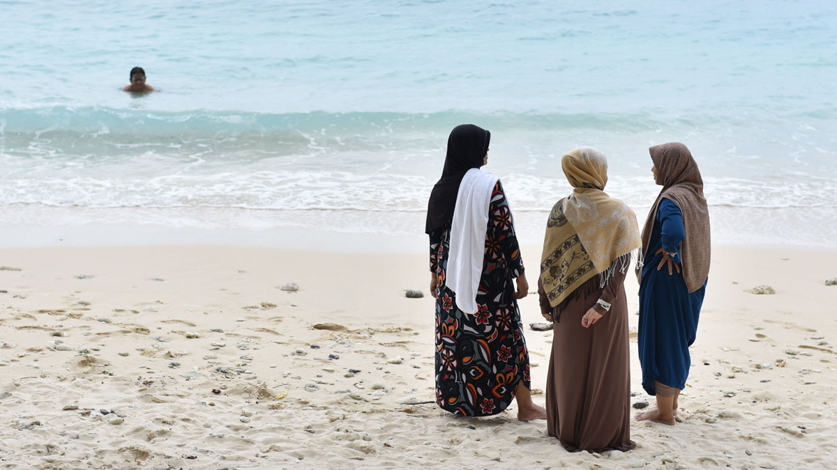 Three women in hijab wait as a boy swims in the ocean in front of the Casa Nemo Beach Resort and Spa of Pulau Weh island, Indonesia.