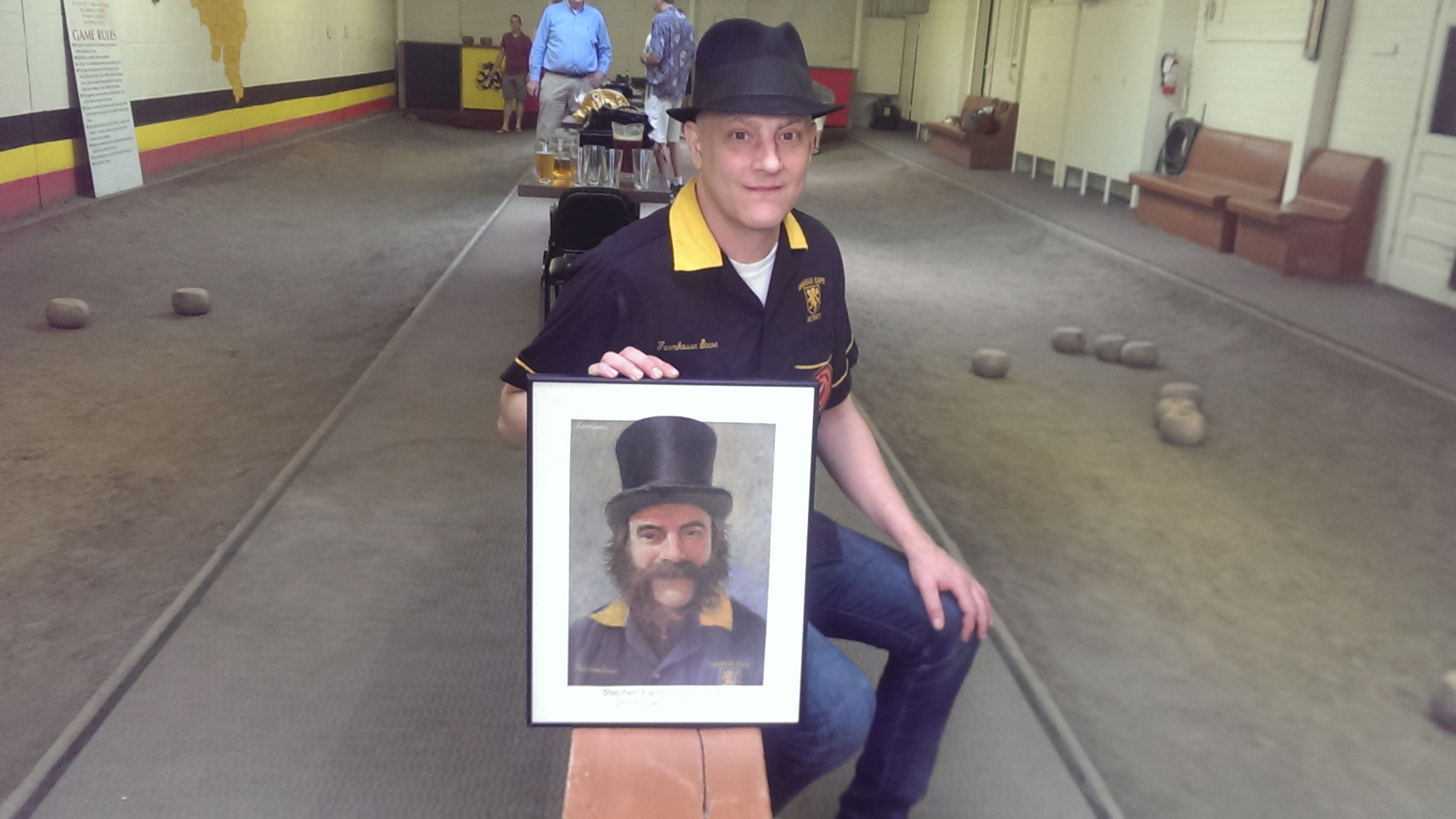 Steve Gosskie, the 2013 Featherbowling chamption in the Cadieux Cafe. Gosskie holds the second portrait that Jerry Lemenu painted for him. The first was stolen and never returned.