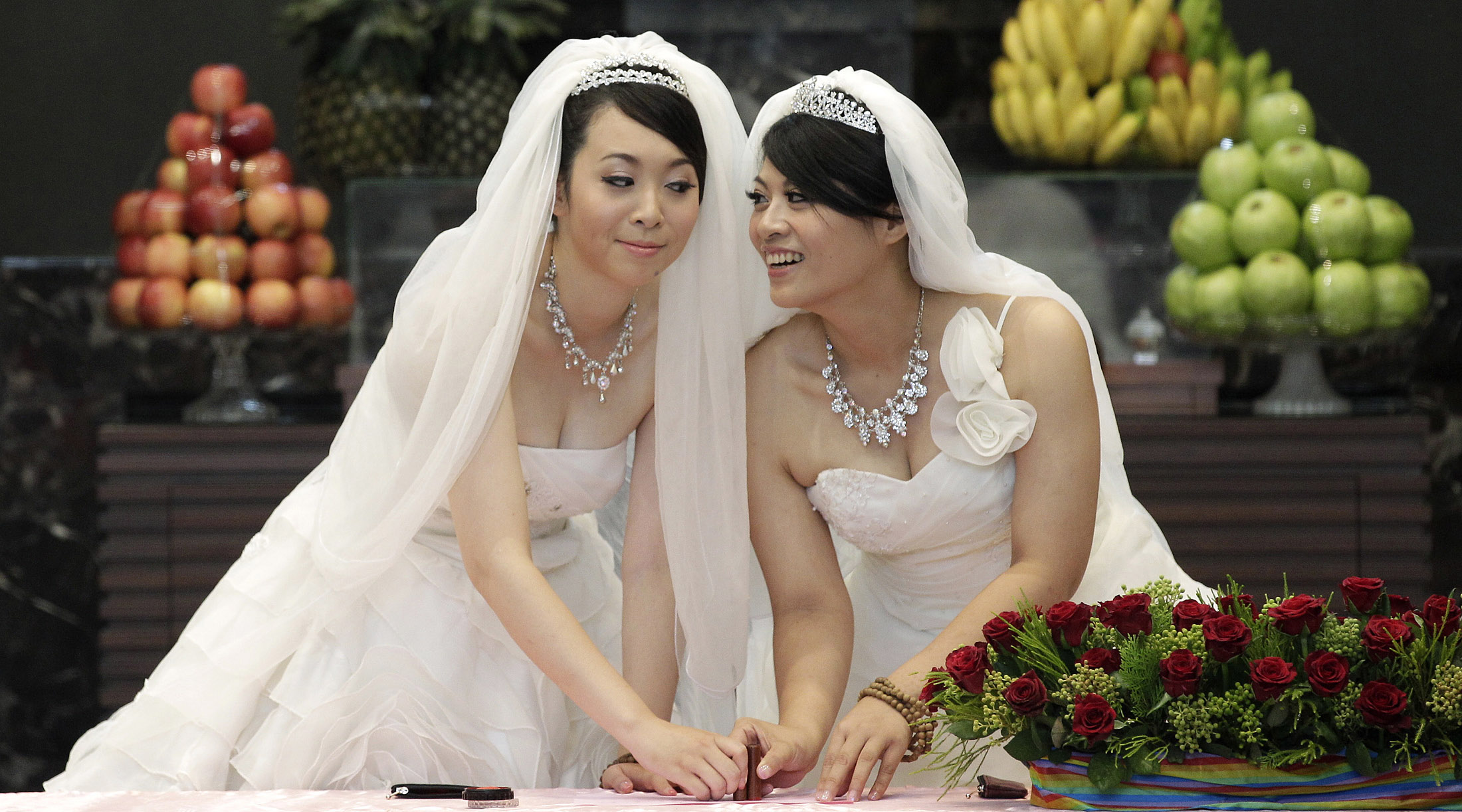 You Ya-ting, left, and Huang Mei-yu cast their stamps during their symbolic same-sex Buddhist wedding ceremony at a temple in Taoyuan county, northern Taiwan, on Aug. 11, 2012.