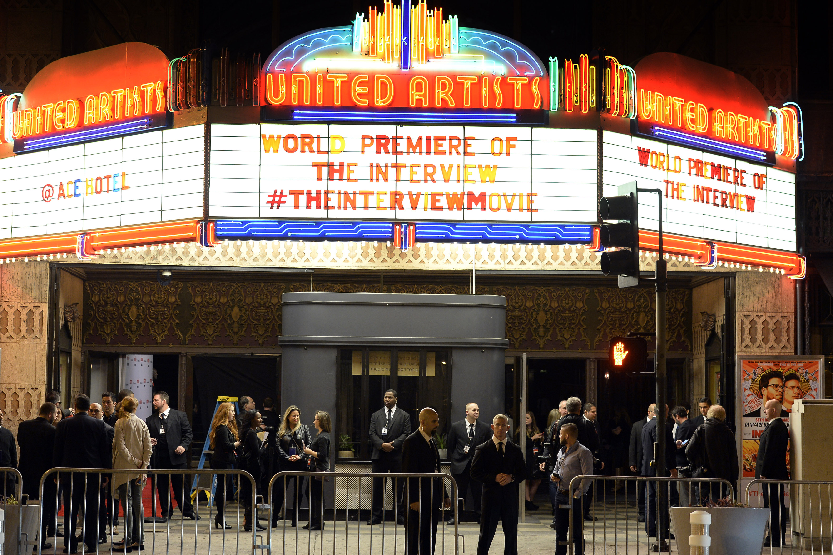 """Security guards stand behind bicycle rails at the entrance of United Artists theater during premiere of the film """"The Interview"""" in Los Angeles, California December 11, 2014."""