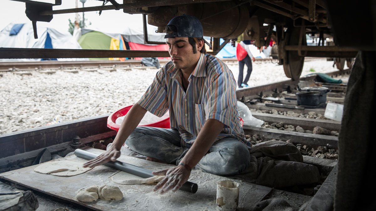 Makmoud Nakarch rolls out dough in order to make Syrian flatbread in his bakery under a cargo train parked at Idomeni Camp.