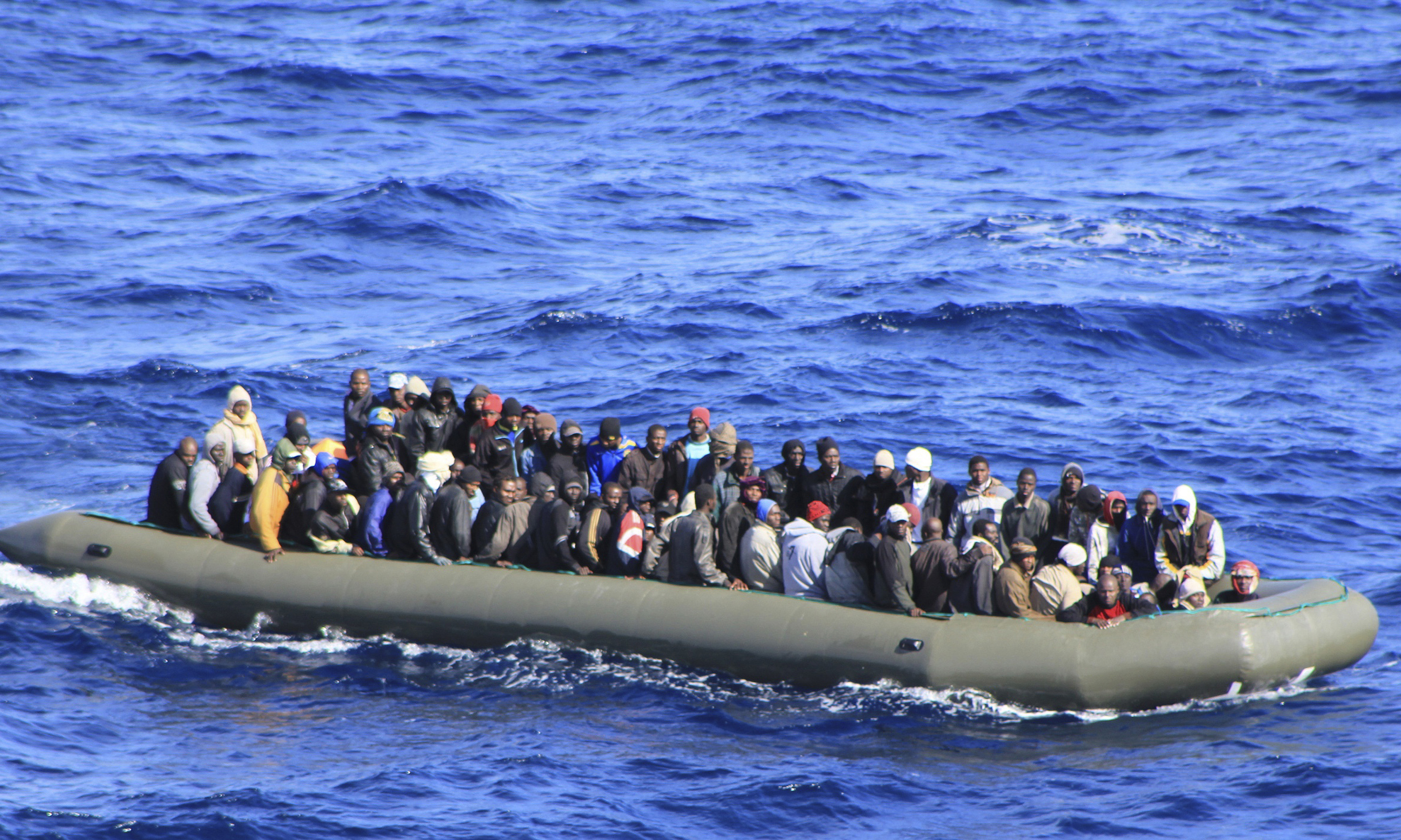 Migrants in a boat during a rescue operation by Italian navy ship San Marco off the coast to the south of the Italian island of Sicily.