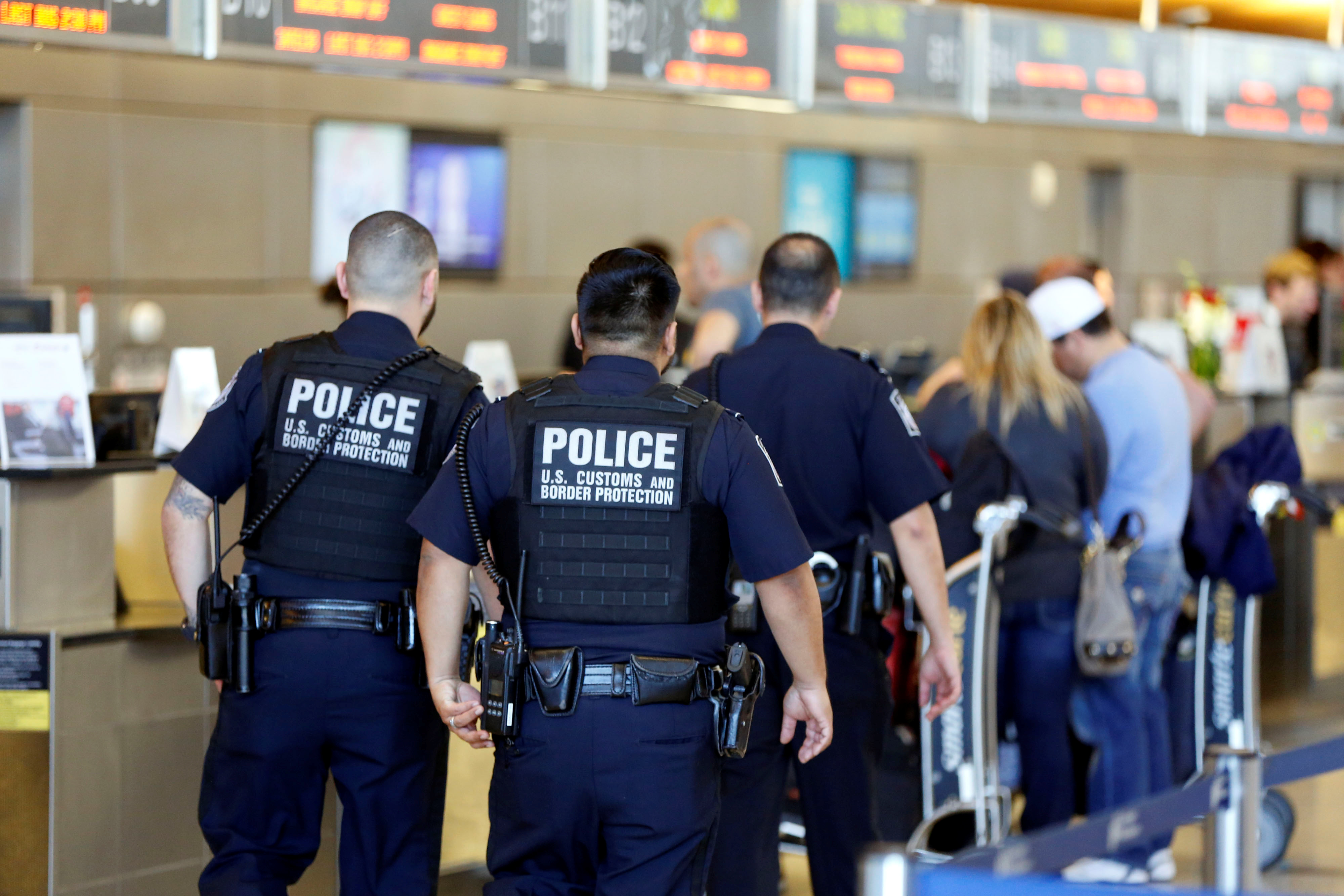 Officers with US Customs and Border Protection walk past ticket counters