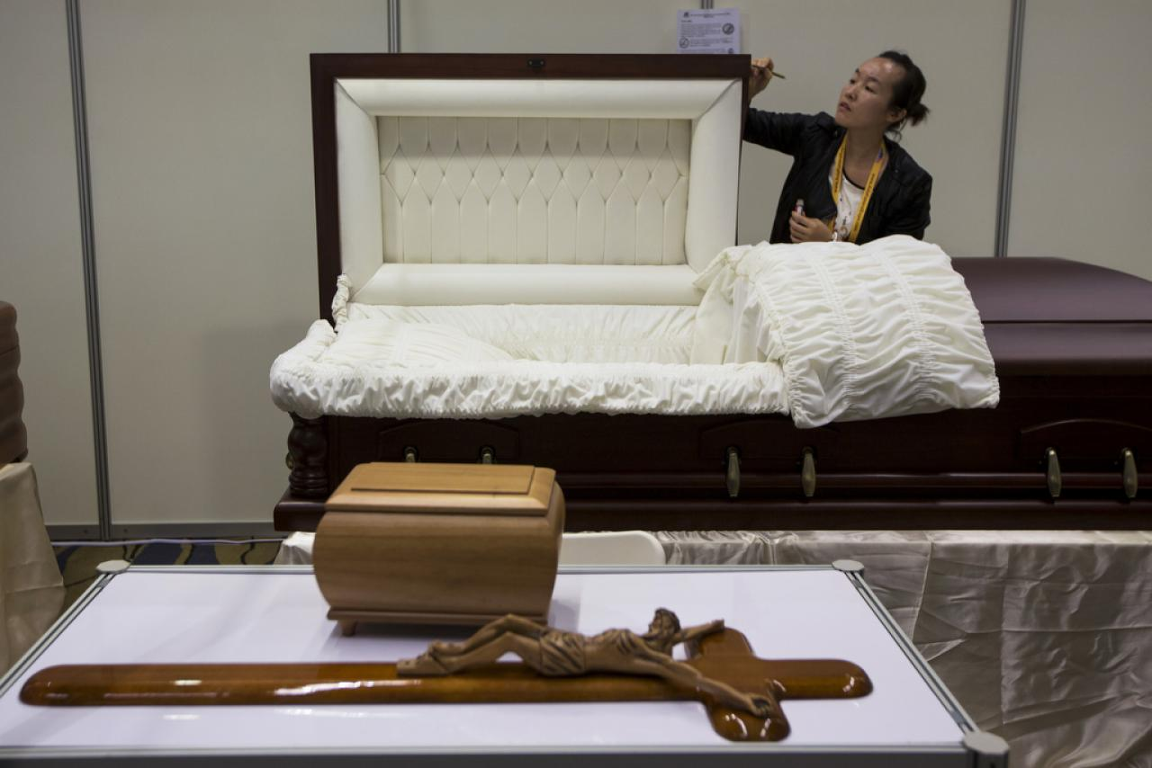 A exhibitor mends a coffin during the Asia Funeral and Cemetery Expo in Macau on May 8, 2014.