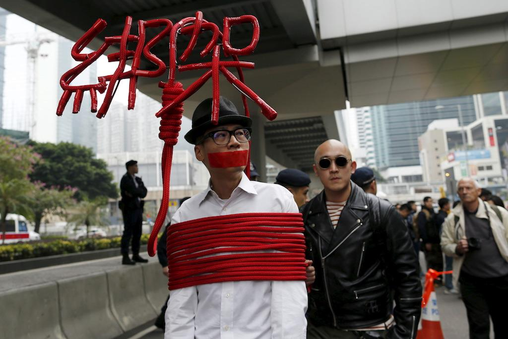 """An artist ties himself with a rope that spells out """"Kidnap"""" during a protest over the disappearance of booksellers in Hong Kong, Jan. 10, 2016."""