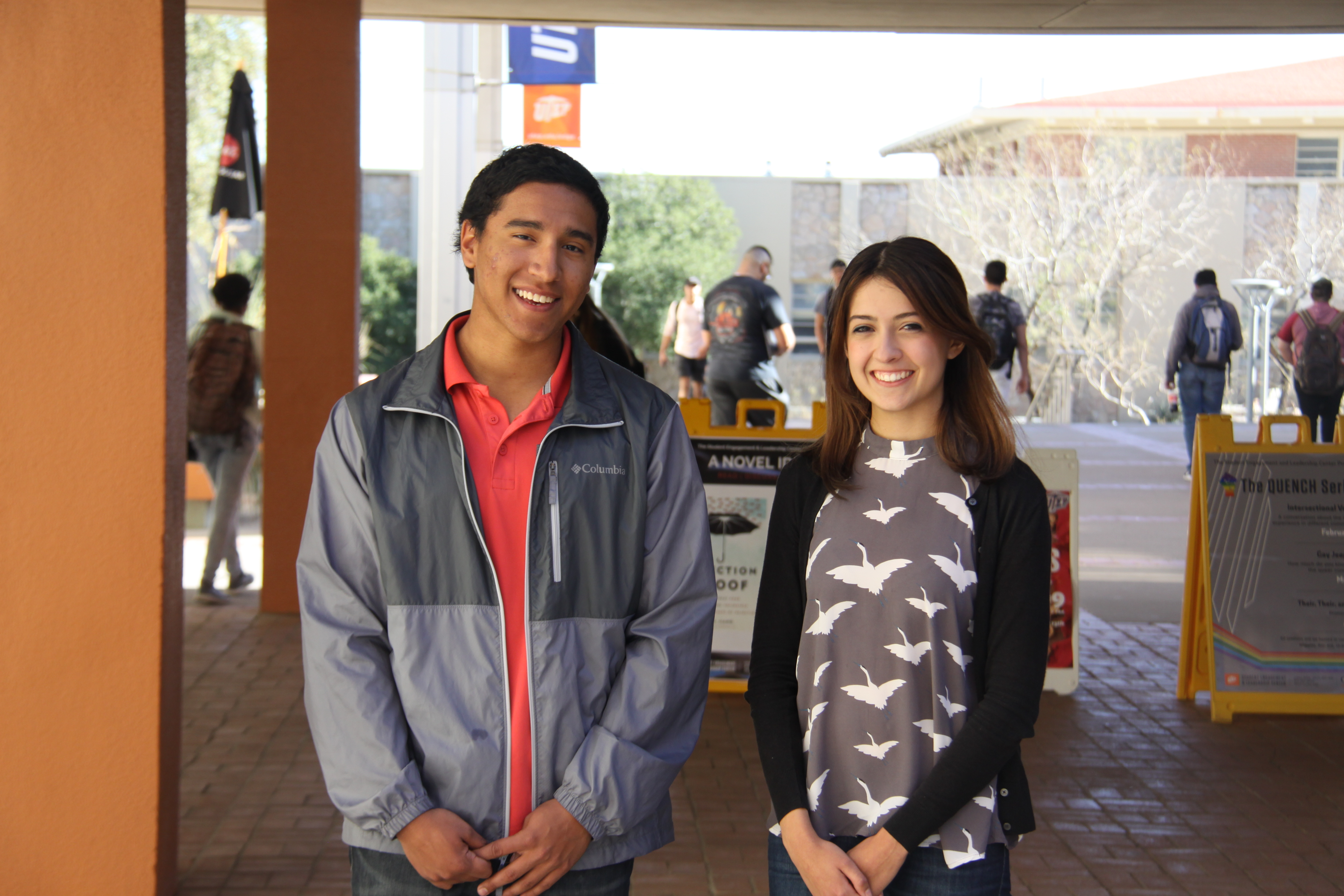 Two college students smile at the camera.