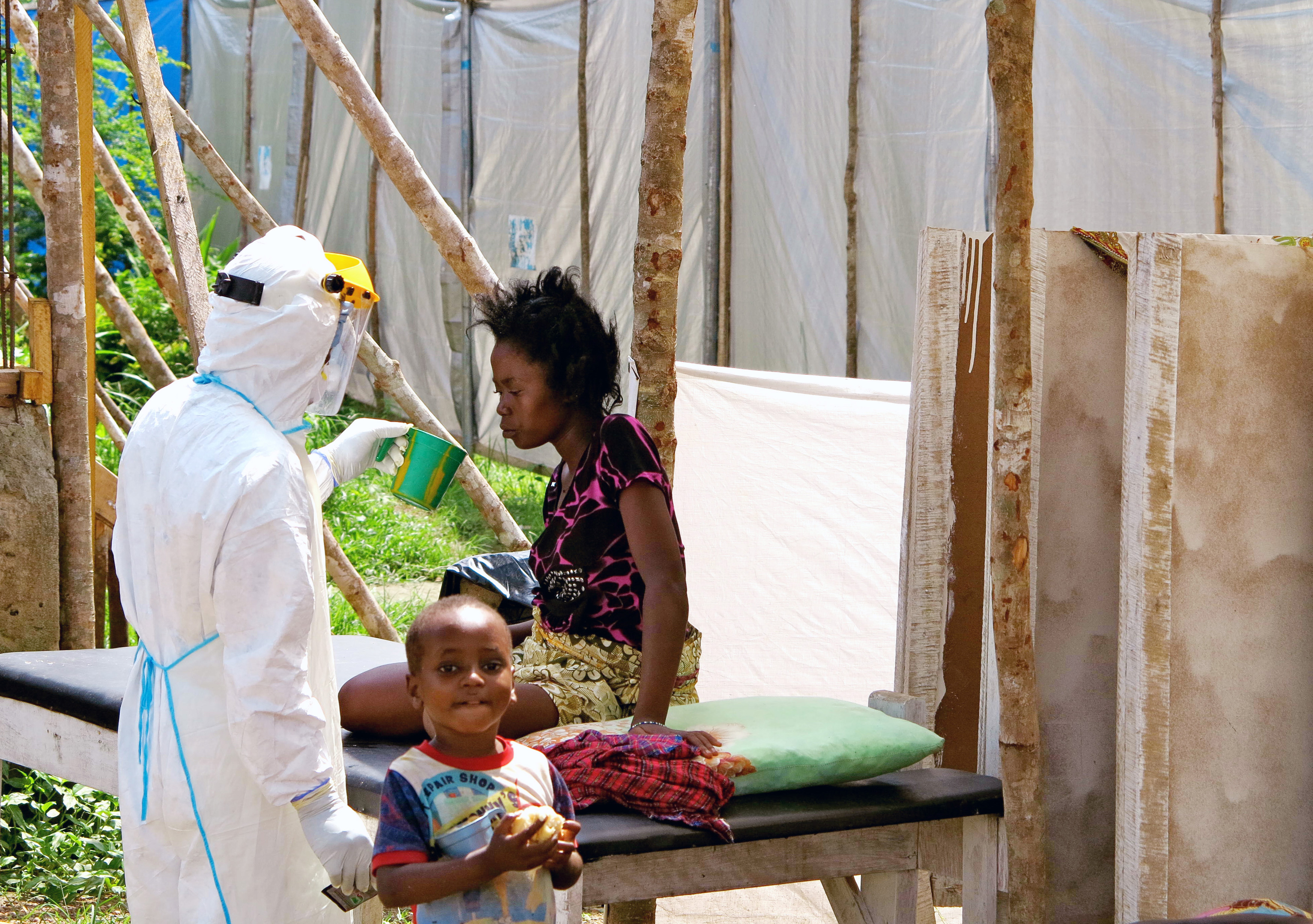 A health worker, wearing head-to-toe protective gear, offers water to a woman with Ebola at a treatment center for infected persons at Kenema Government Hospital in Kenema, Sierra Leone.