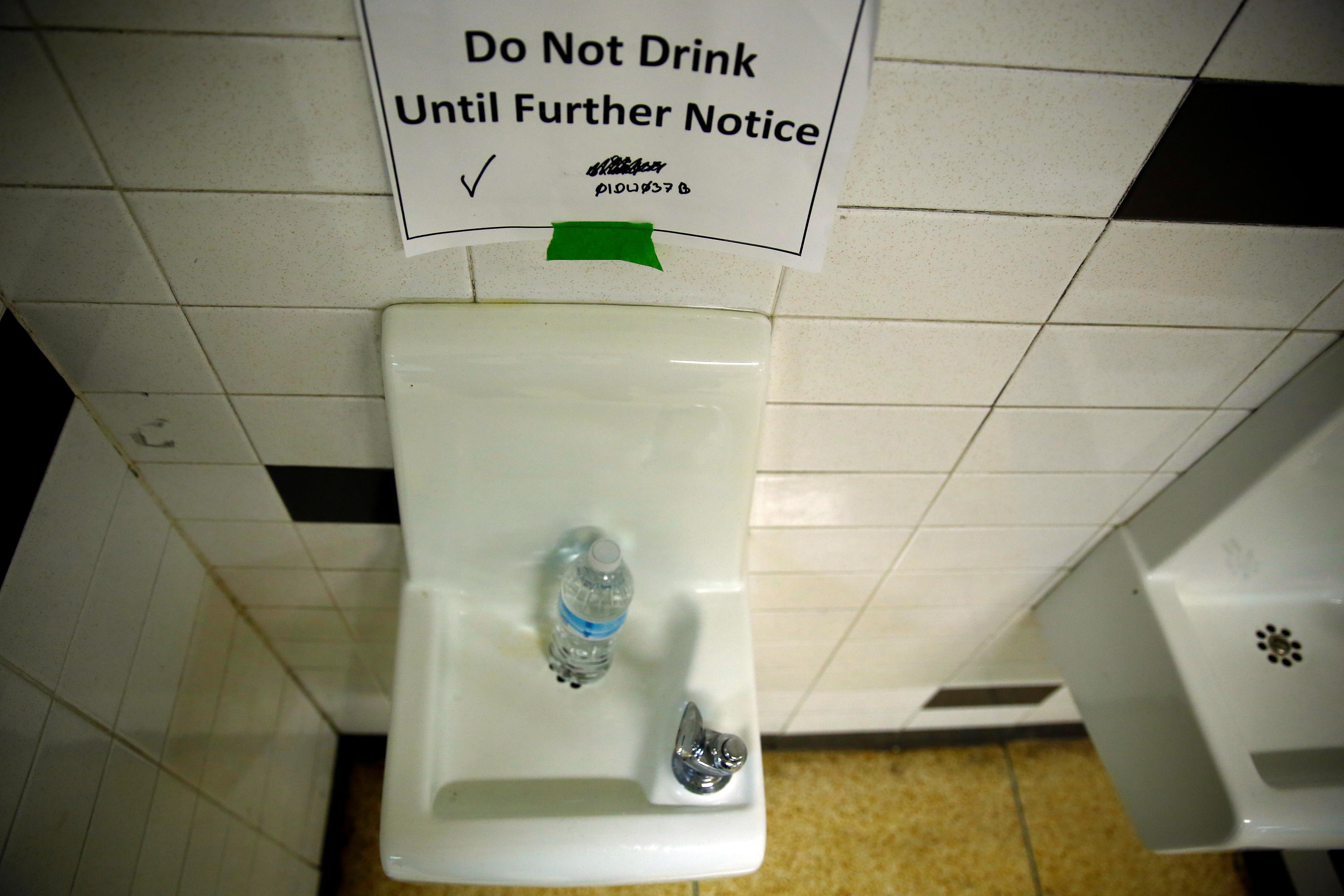 A sign is seen next to a water dispenser at a high school in Flint