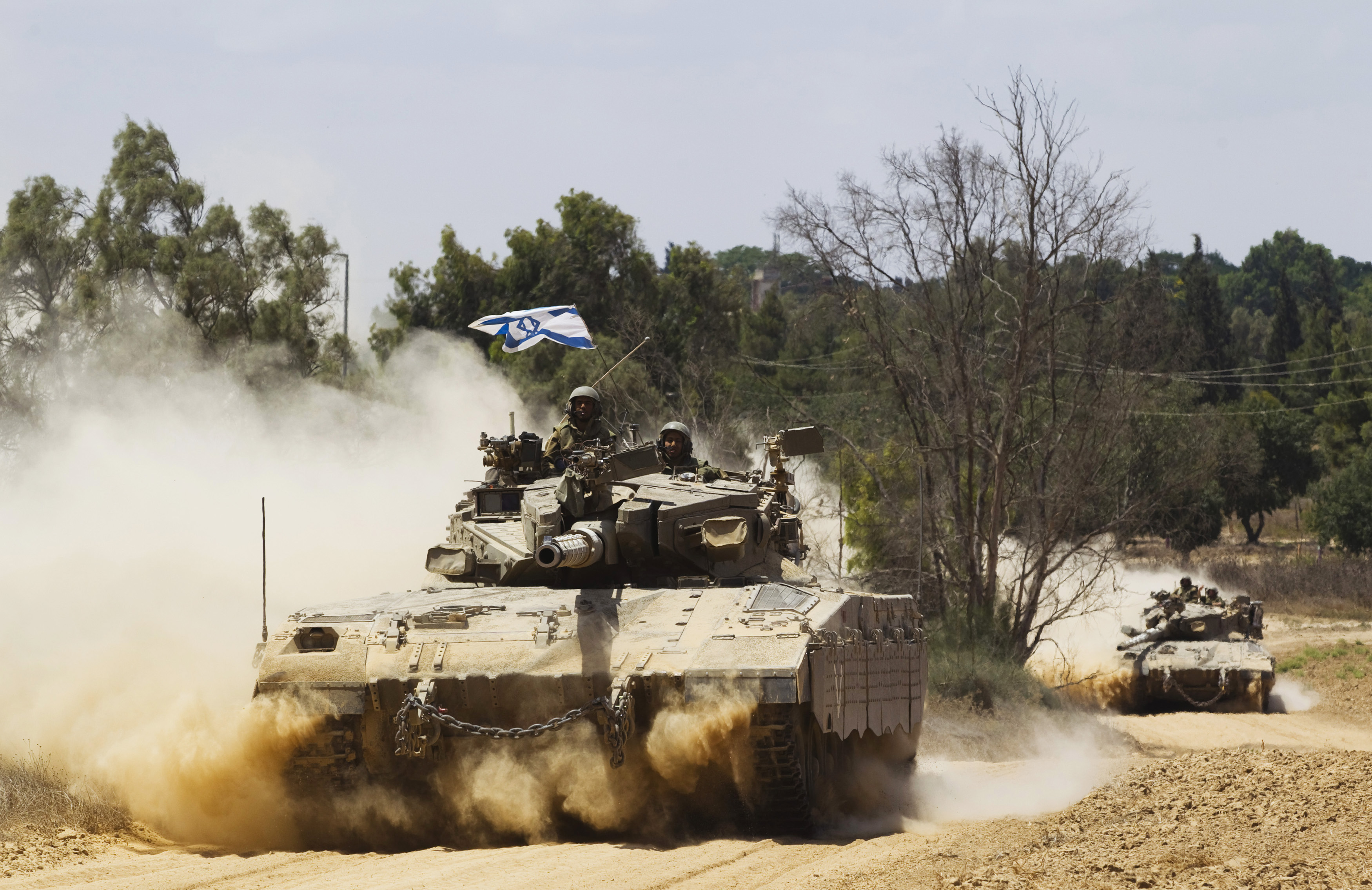 "Israeli soldiers travel atop tanks outside the Gaza Strip July 18, 2014. Israel stepped up its land offensive in Gaza with artillery, tanks and gunboats on Friday and declared it could ""significantly widen"" an operation Palestinian officials said was kill"
