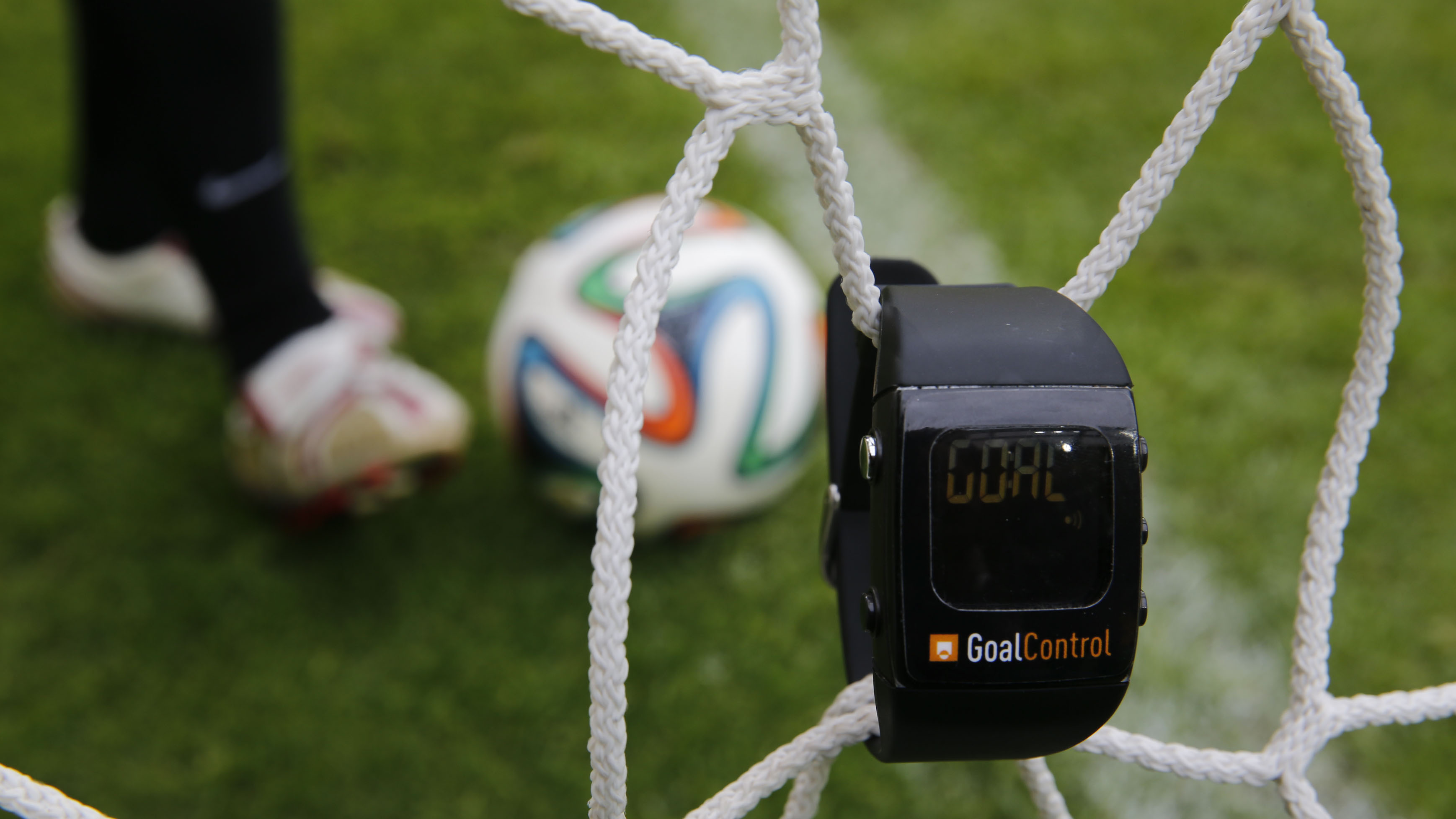 """A GoalControl watch reads """"goal"""" as a football rolls fully behind the goal line during a demonstration in the western German city of Aachen May 28, 2014. German firm GoalControl has been appointed by FIFA as the official provider for the goal-line technol"""