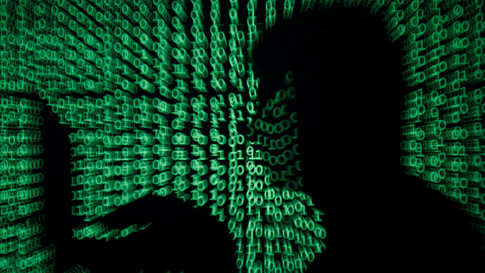 A man holds a laptop computer as cyber code is projected on him in this illustration.