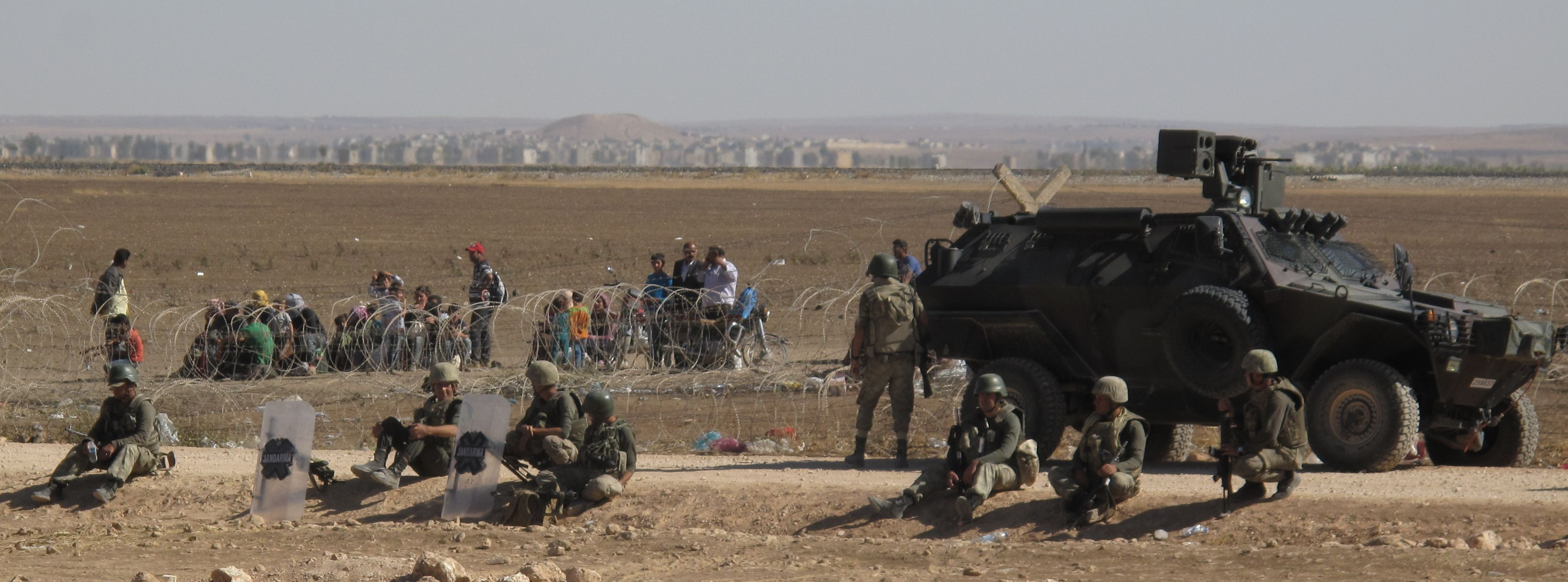 Scores of Syrian refugees from Kobane - under threat of capture by Islamic State - sit in the sun waiting to be allowed to cross into Turkey. Sept. 26, 2014. The outskirts of the village are visible in the background.
