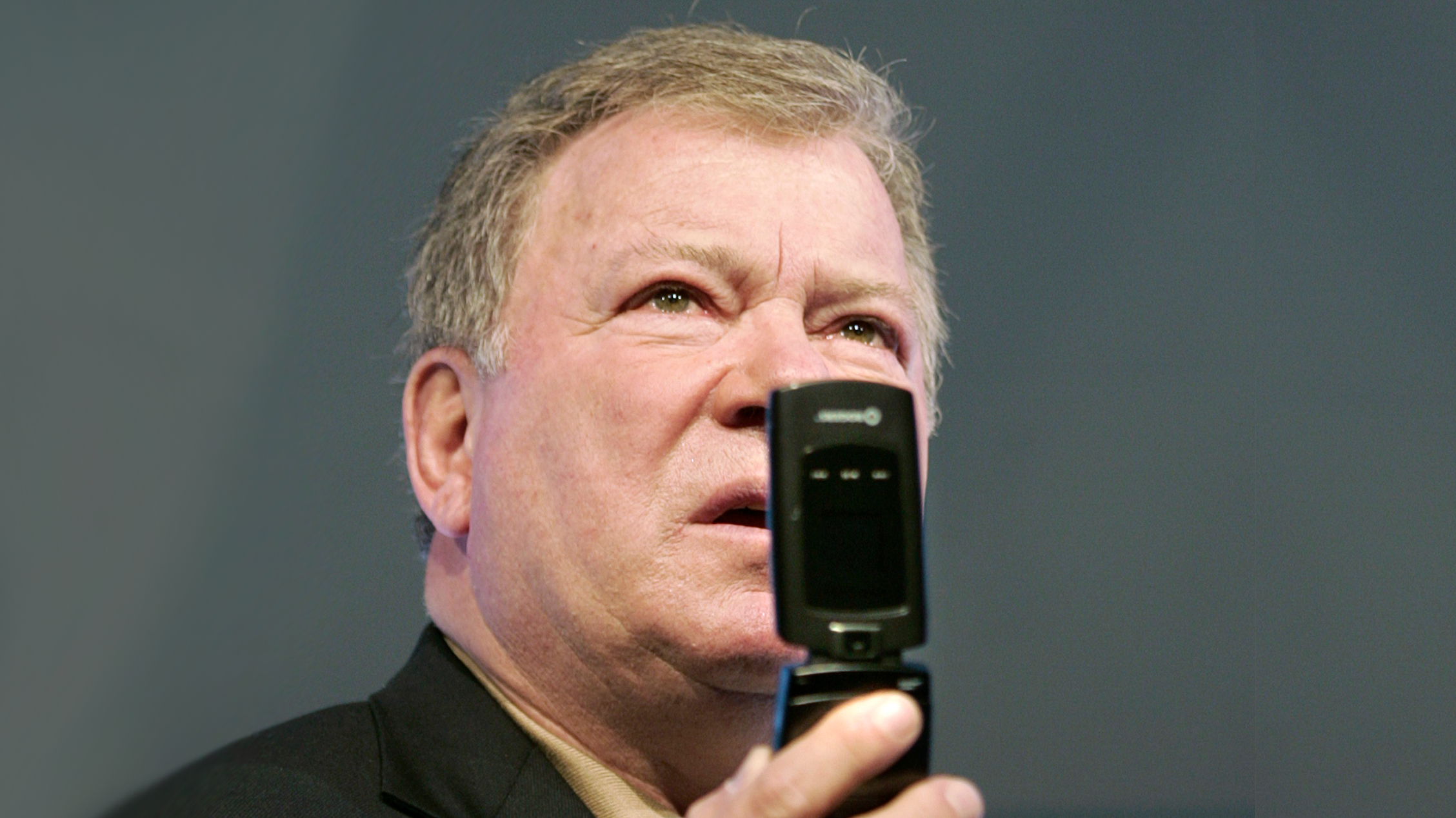 William Shatner, in a pose similar to his Star Trek character Captain Kirk using his communicator, unveils North America's first real-time video conferencing cell phone during a news conference in Toronto April 2, 2007.
