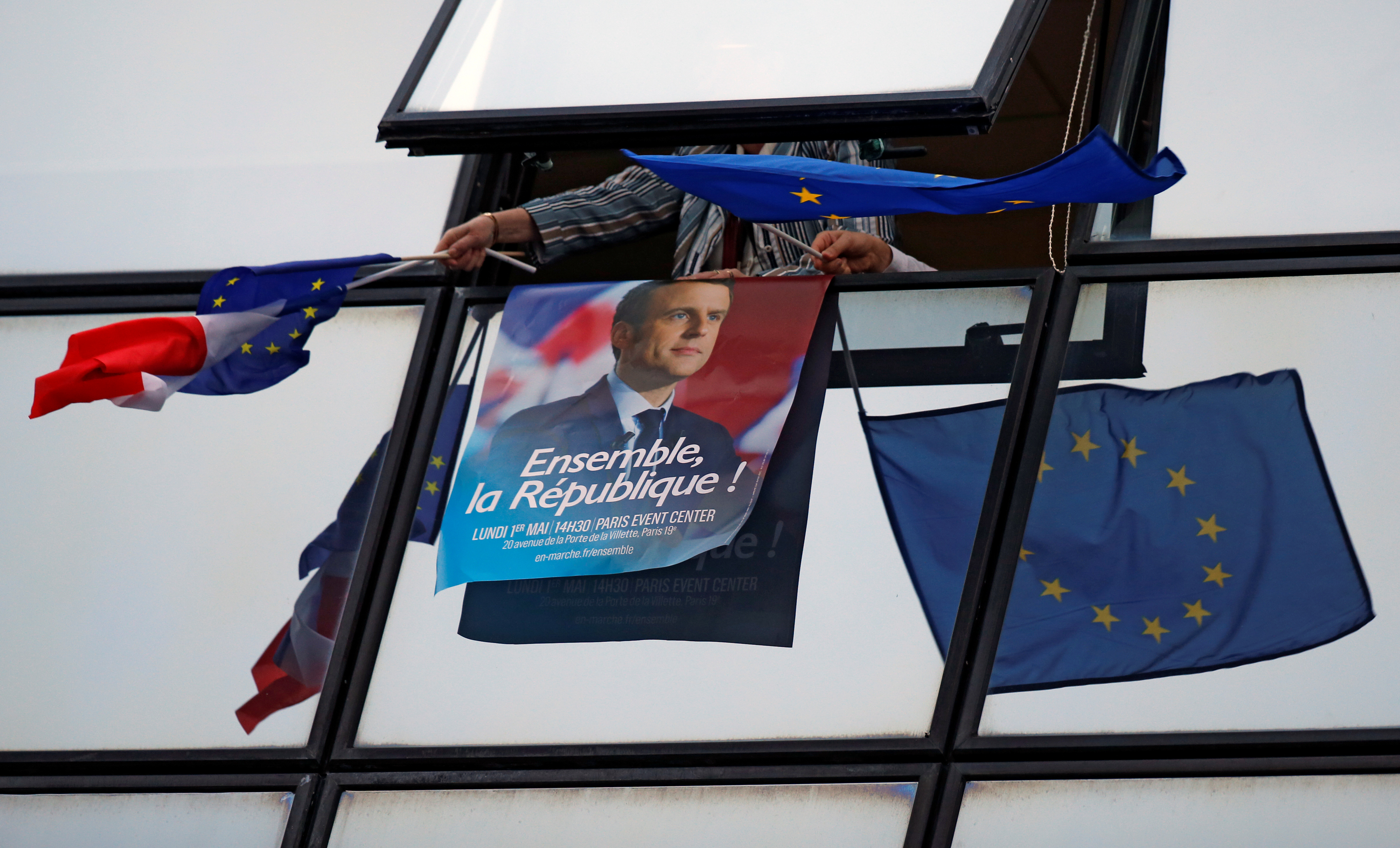 A supporter holds a campaign poster of Emmanuel Macron and European Union flags