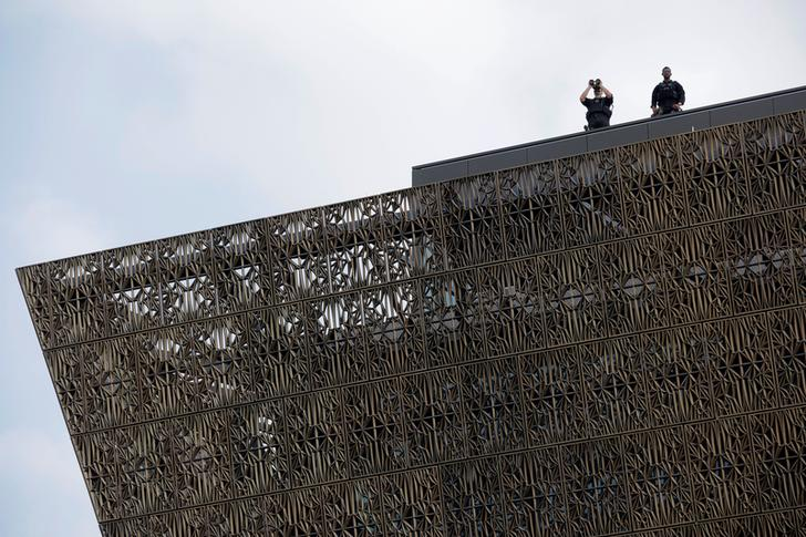 Two Secret Service agents stationed on the roof of the National Museum of African American History and Culture use binoculars to survey the crowd during the Museum's opening ceremony on September 24, 2016.