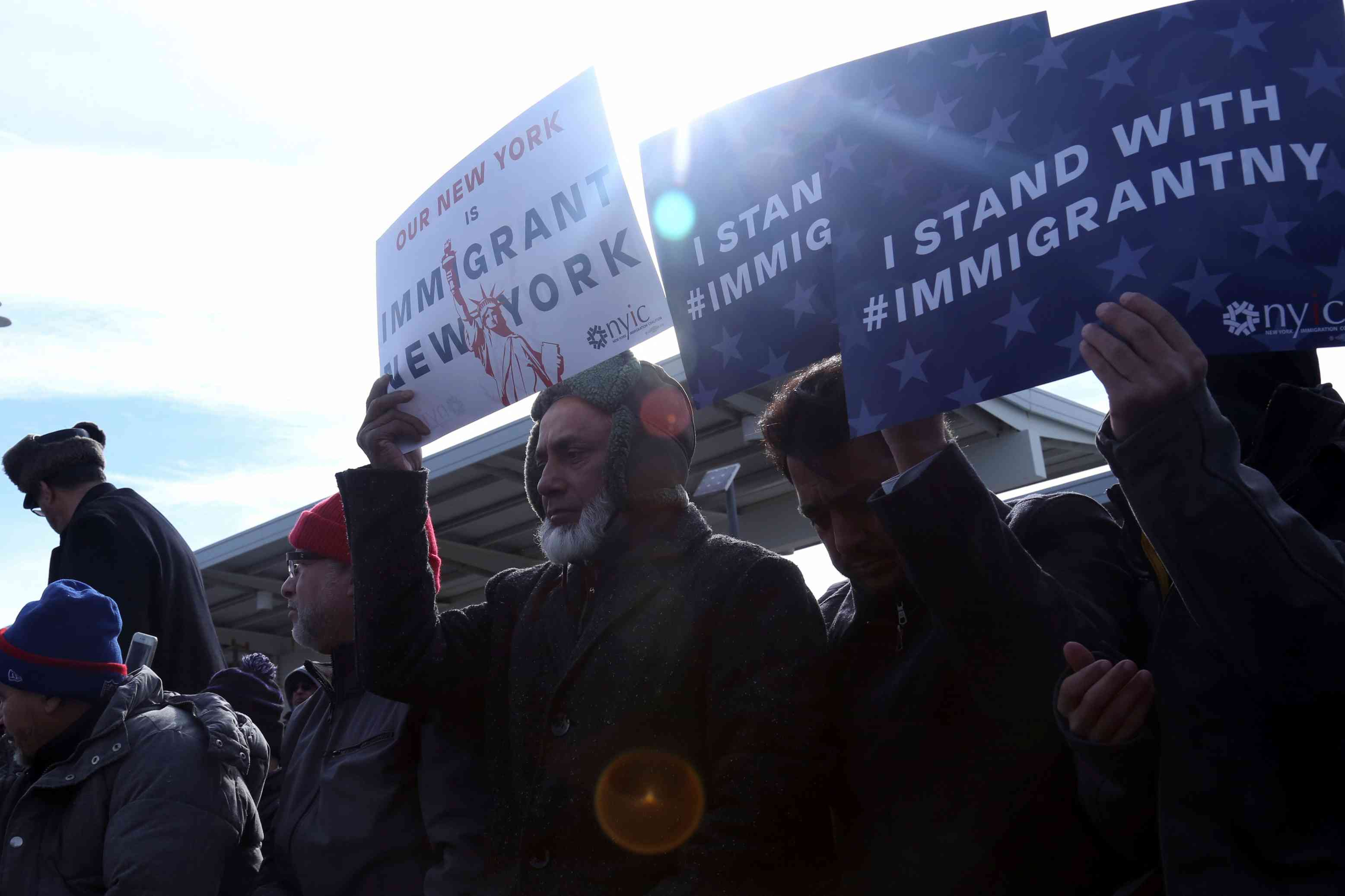 People hold signs during an interfaith action and Jummah prayer outside Terminal 4 at John F. Kennedy Airport in New York, U.S., February 3, 2017.
