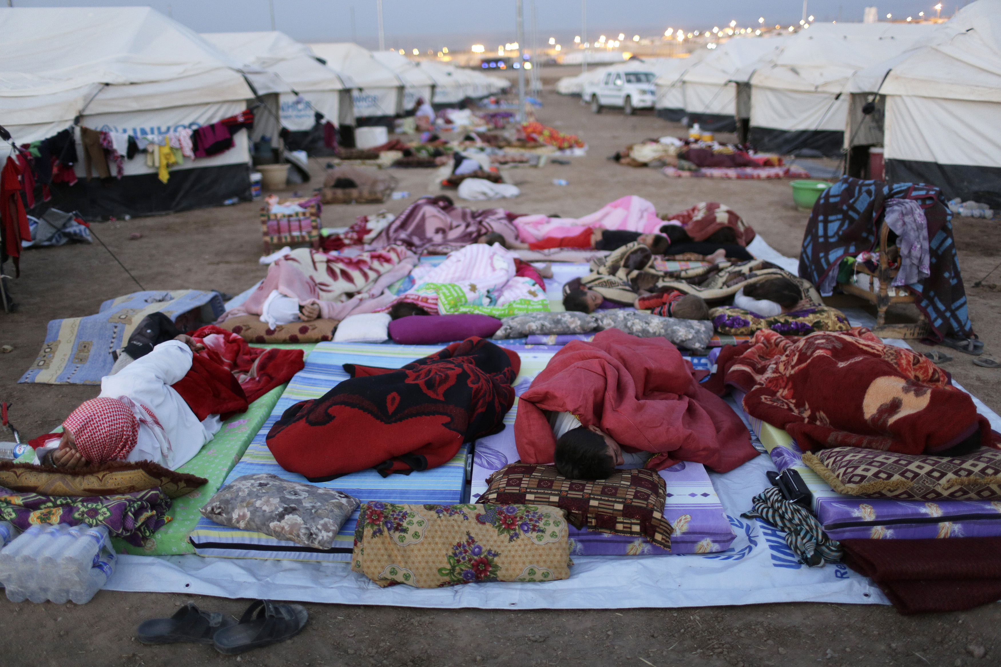 Displaced people from the minority Yazidi sect, who fled violence in the Iraqi town of Sinjar, sleep on the ground at the Bajed Kadal refugee camp in southwest Dohuk province on August 23, 2014.