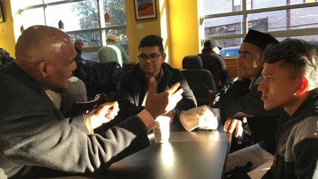 (From right) Muhammad Anwar and Hussein Muhammad (wearing a hat) chat with Ibrahim Rashid, an intern with IINE (center), and a community member.