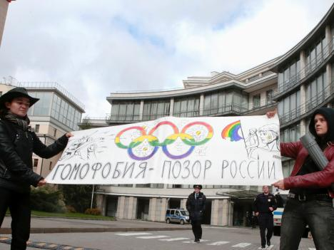 Gay rights activists in Moscow hold a banner protesting a ban on gay pride parades during the Sochi 2014 Winter Olympics.