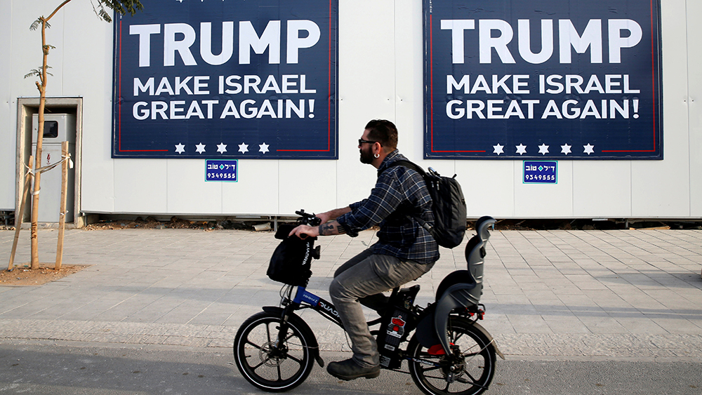 A man cycles past signs bearing the name of U.S. President-elect Republican Donald Trump in Tel Aviv, Israel.