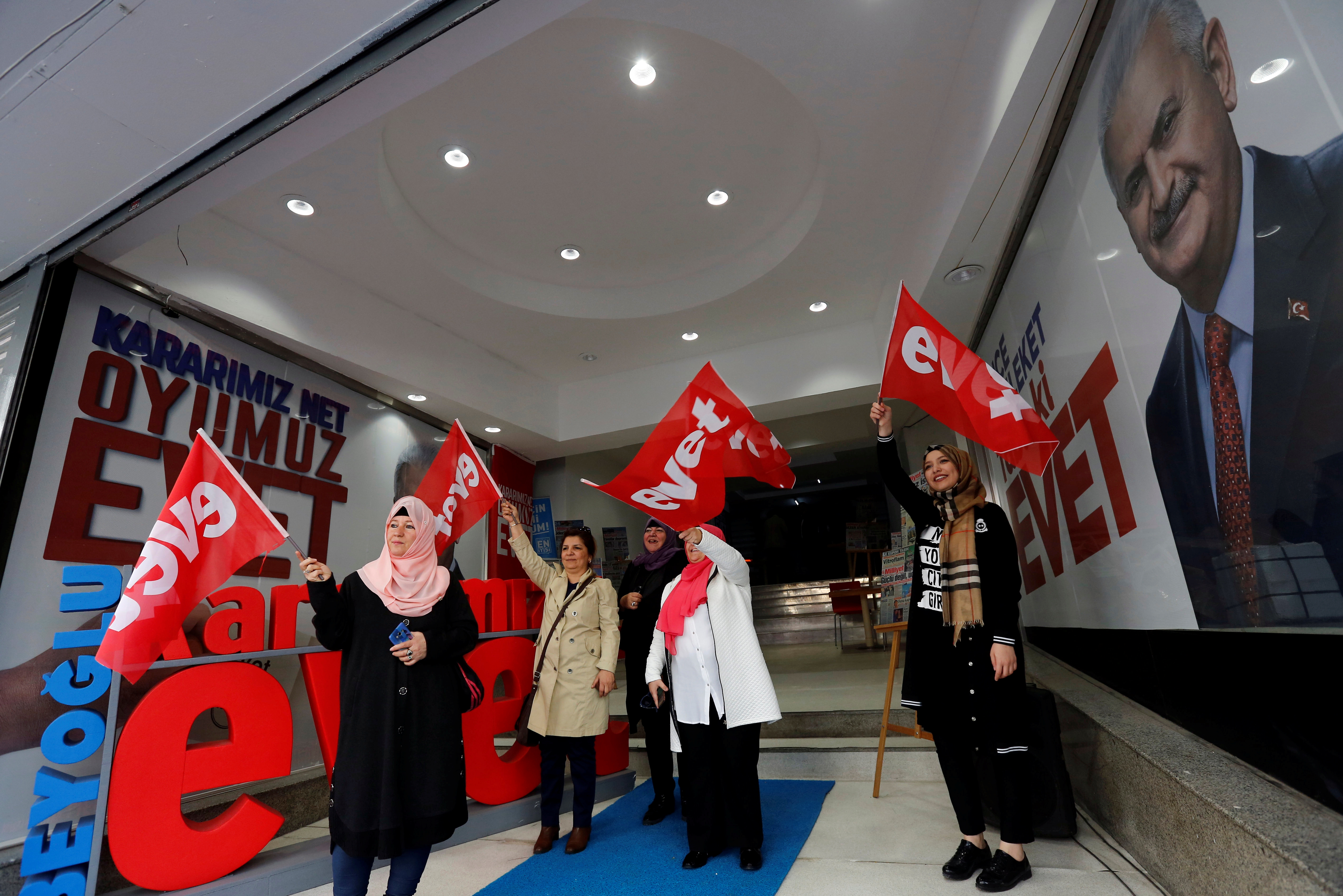 """Women wave """"Yes"""" flags at a campaign office of the ruling AK Party"""