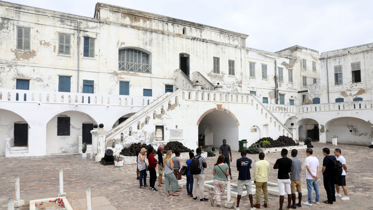 Several people are shown standing around a tour guide in front of the white facade of the Cape Coast Castle.