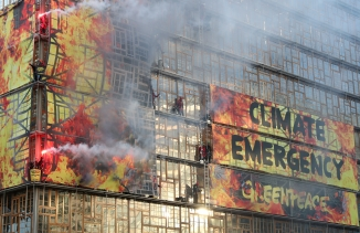 "Building reads ""climate emergency"" with flares of red and orange hues on the front of the building"