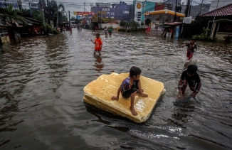 Children play in the floodwaters after heavy rains in Bekasi, near Jakarta, Indonesia, Feb.25, 2020.