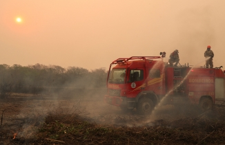 Firefighters work to extinguish a fire in a ranch amongst smoke in thePantanal, the world's largest wetland, in Pocone, Mato Grosso state, Brazil, Aug.28, 2020.
