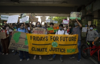 Student activists carry posters and shout slogans as they participate in a protest march against climate change in Delhi, India, March 19, 2021.