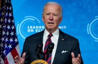 US President Joe Biden is shown standing at a podium wearing a suit and tie with an US flag to his right.