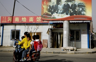 Children ride on a motorcycle near a large billboard.