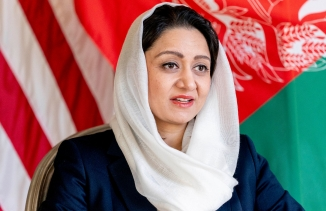 Roya Rahmani in a dark blue outfit and white hijab sitting in front of the US and Afghan flags