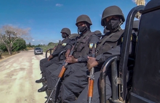 In this image made from video, Rwandan policemen patrol near the Amarula Palma hotel in Palma, Cabo Delgado province, Mozambique, Sunday, Aug. 15, 2021.
