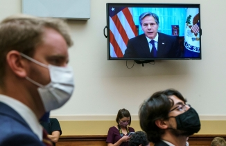US Secretary of State Antony Blinken is shown on a TV hanging on the wall in the distance with several people wearing face masks stand in the nearground.