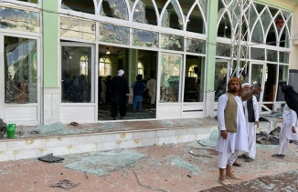 Three men are show wearing white traditional clothing and standing amidst broken glass from a mosque in the background.