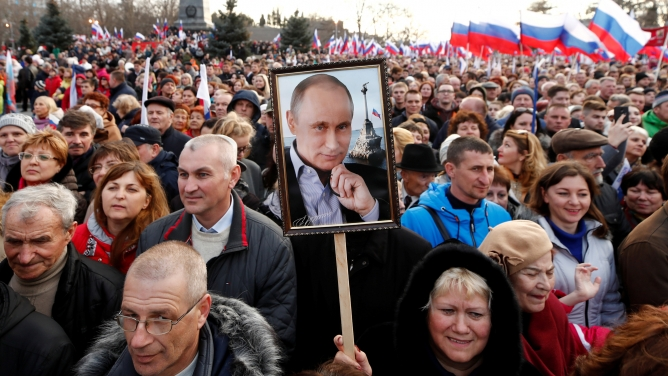 People attend a rally marking the fourth anniversary of Russia's annexation of Ukraine's Crimea region with signs praising President Vladimir Putin