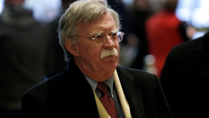 Former US Ambassador to the United Nations John Bolton walks through a lobby wearing a scarf and overcoat.