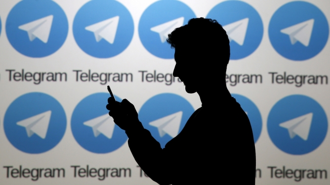 Two men pose with smartphones in front of a screen showing the Telegram logo.