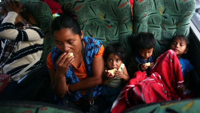 Central American migrants moving in a caravan on a bus through Mexico are seen eating.