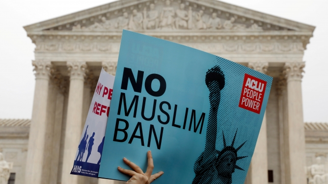 "Protesters outside the US Supreme Court carry signs saying ""No Muslim ban."""