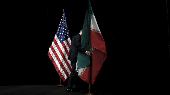 A staff member removes the Iranian flag from the stage at the Vienna International Center in Austria.