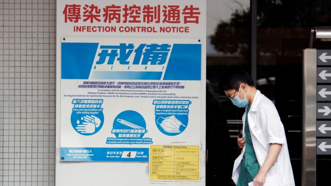 A medical personnel walks past a notice on flu alert at a hospital Hong Kong.